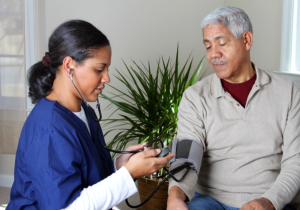 caregiver taking blood pressure to his patient