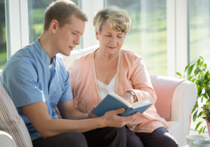 caregiver reading book to an old woman